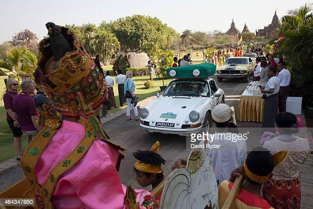 Locals perform a ceremony to welcome participants after they cross the finish line at the Aureum Palace Hotel on the final day of the Road to...