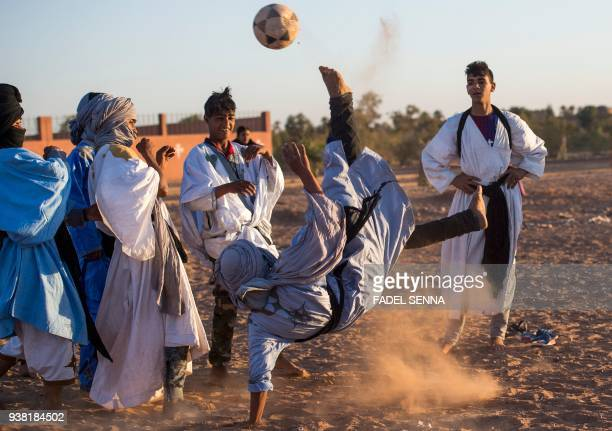 TOPSHOT Locals play football during the 15th International Nomad Festival in Mhamid elGhizlane in Morocco's southern Sahara desert on March 24 2018