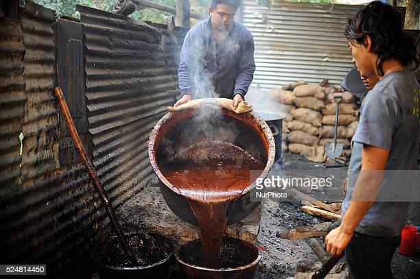 Locals pouring Molten Raw Hardened molasses on mud bucket to prepare molasses Chaku on 06 January 2015 at Tokha Kathmandu Nepal for the celebration...