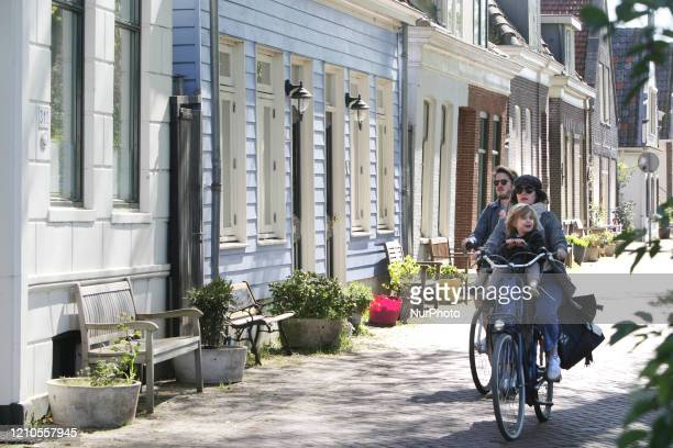 Locals residents ride bicycle on the Nieuwendammerdijk street with old antique houses from 1609 on April 20 2020 in AmsterdamNetherlands Dutch Prime...