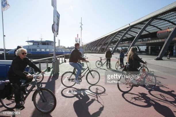 Locals ride bicycles disembarking on the ferry practice social at the IJ river near central station on April 20 2020 in AmsterdamNetherlands Dutch...