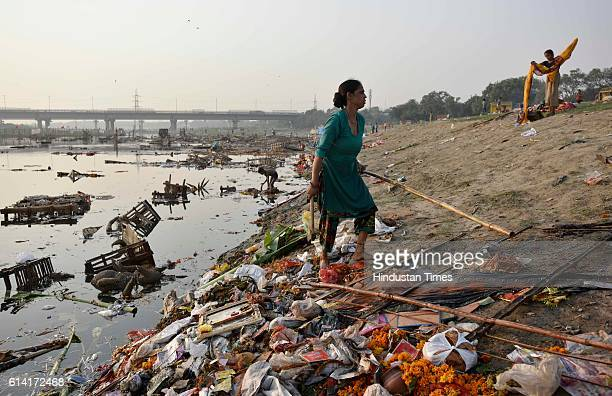 Locals scavenge for the remains of Goddess Durga idols after the immersion in the River Yamuna near ISBT on October 12 2016 in New Delhi India...