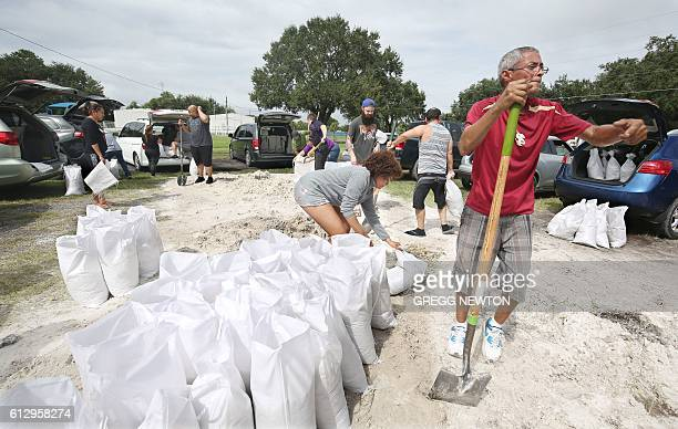 Locals scramble to fill sandbags with the last of a supply at the Road and Bridge Department in Kissimmee Florida in preparation for the landfall of...