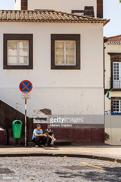 locals seated streetside making conversation - merten snijders stockfoto's en -beelden