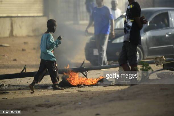 Locals set tyres on fire and block a sidestreet leading to their neighbourhood in the Sudanese capital Khartoum to stop military vehicles from...