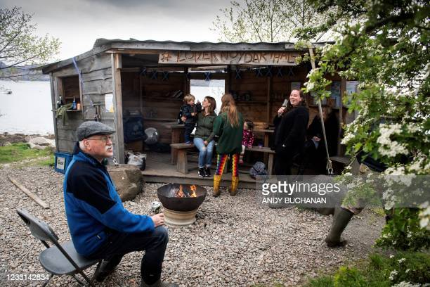 Locals sit and drink at 'The Table', a wooden shed near The Old Forge pub, in Inverie on the Knoydart peninsular in the Scottish Highlands on May 21,...