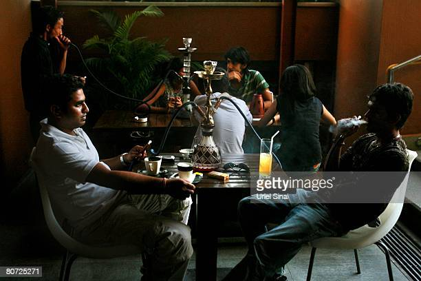 Locals sit at a coffee shop on April 14 2008 in Bangalore India Many residents work for multinational cooperations and the economy is booming New...