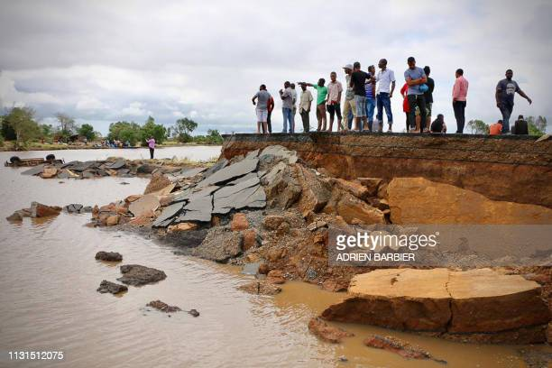 Locals stand beside a damaged section of the road between Beira and Chimoio in Nhamatanda district central Mozambique on March 19 after the area was...