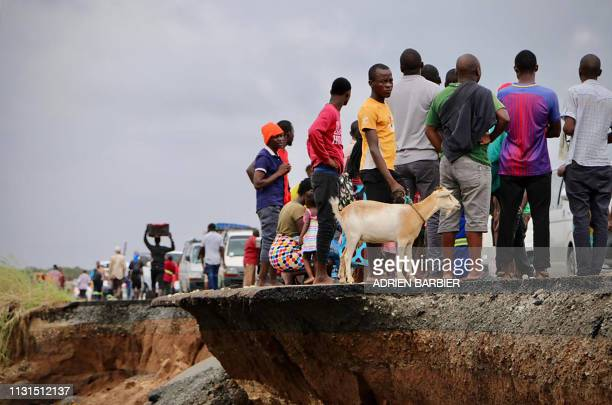 Locals stand beside a damaged section of the road between Beira and Chimoio in Nhamatanda district, central Mozambique, on March 19 after the area...