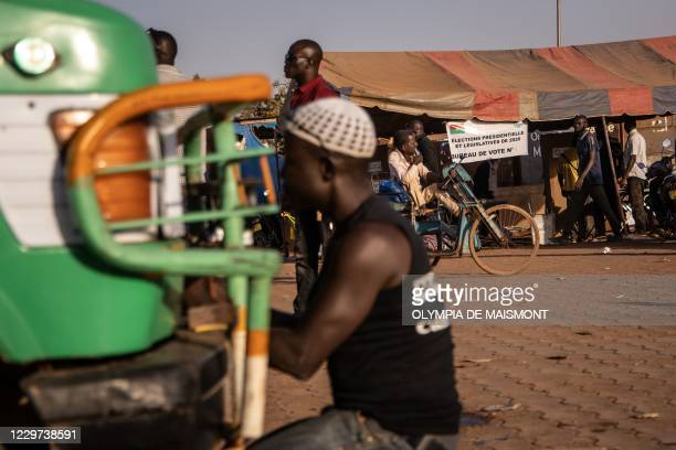 Locals stand in front of a polling station in a bus station in Ouagadougou on November 22 during Burkina Faso's presidential and legislative...