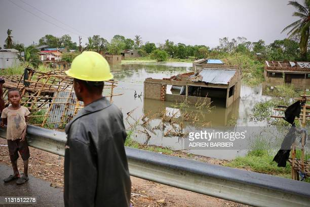 Locals stand near the flooded village of Tica, central Mozambique, on March 19 after the area was hit by the Cyclone Idai. - Rescue workers in...