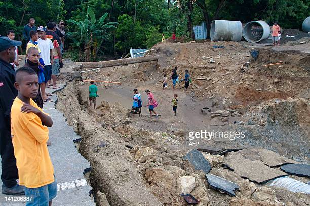 Locals stand next to a collapsed section of a freeway following heavy rains in Port Moresby on March 13 2012 An electrical storm and torrential rain...