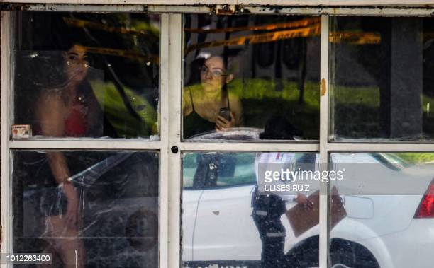 Locals stare at the crime scene from a window after a man was shot dead in Guadalajara Jalisco State Mexico on August 1 2018 Mexican Presidentelect...