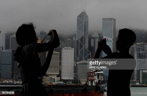 Locals take photos of the skyline after a typhoon hit Hong Kong on September 15 2009 Tropical storm Koppu caused the No 8 typhoon signal to be...