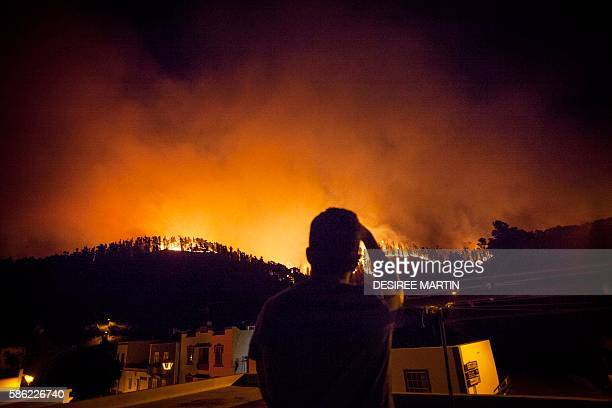 Locals take snapshots during a forest fire approaching few meters from the village of Fuencaliente on the Spanish Canary island of La Palma on August...