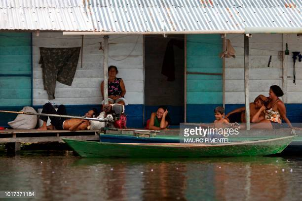 Locals talk in their front door at Raimundo do Jaraua village state of Amazonas Brazil on June 27 2018 The fact of inhabiting the largest rainforest...