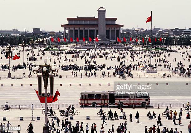 Locals travel through while others gather at Tiananmen Square with the Mausoleum of Mao Zedong and the Monument to the People's Heroes visible in the...