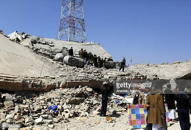 Locals try to rescue people who were buried in the wreckage of Sana'a Police Headquarters after Saudiled coalition carried out airstrikes in the El...