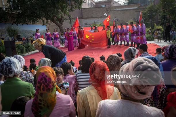 TOWN KASHGAR XINJIANG CHINA Locals Uyghur seen watching the traditional Uyghur dancing show while the dancers holds Chinese flags before starting the...