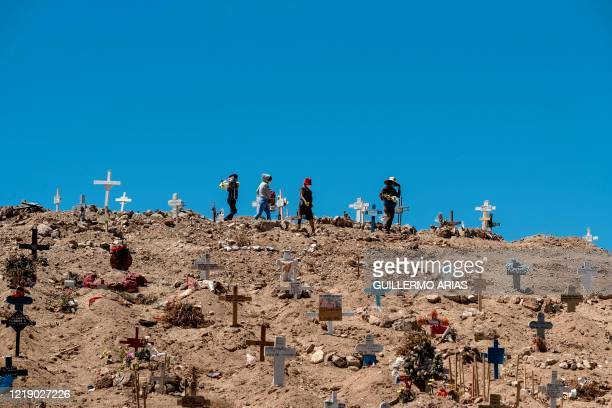Locals visit the graves of their relatives at the Municipal Cemetery in Tijuana, Baja California state, Mexico on June 9 amid the COVID-19 pandemic.