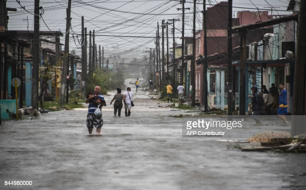TOPSHOT Locals wade through a flooded street after the passage of Hurricane Irma at Caibarien Villa Clara province 330km east of Havana on September...