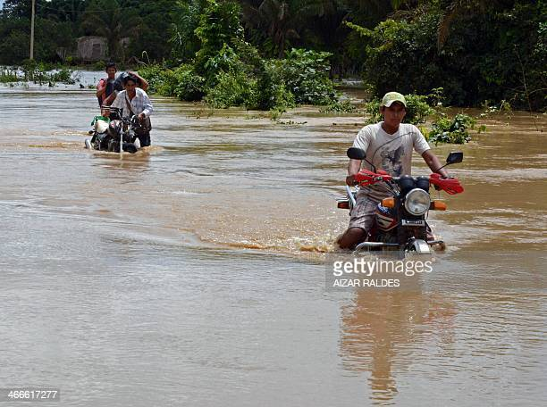 Locals wade through a highway flooded by the overflowing of the Beni river and heavy rains hitting the country in Reyes department of Beni northeast...
