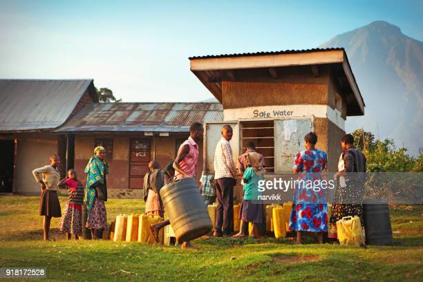 locals waiting to get drinking water in ugandan village - uganda stock pictures, royalty-free photos & images