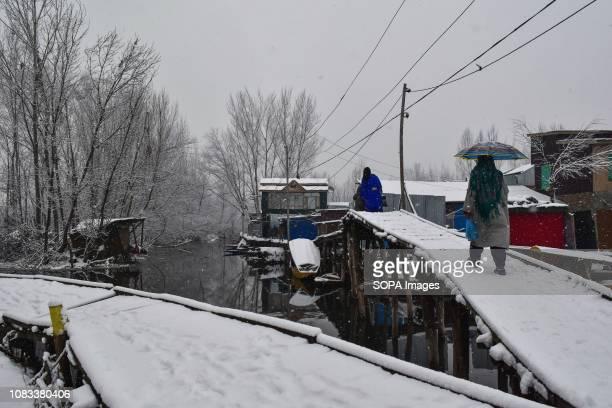Locals walk on foot bridge in the interiors of Dal Lake during heavy snowfall in Srinagar Indian administered Kashmir Fresh snowfall began in Kashmir...