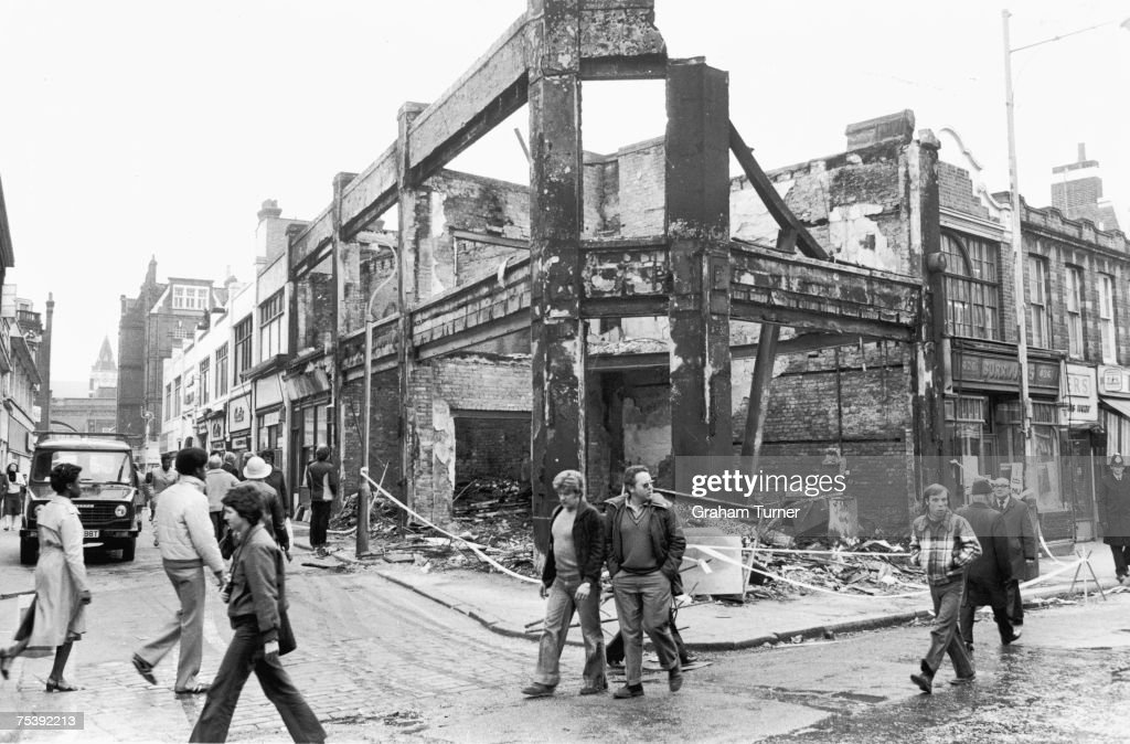 Locals walk past a building destroyed during the second night of rioting in Brixton, 13th April 1981.