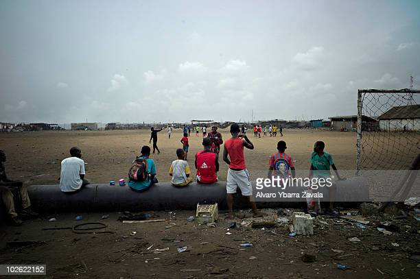 Locals watch a local football team taking part in training on the main pitch in the Agbogbloshie slum in Accra Ghana There are many young people in...