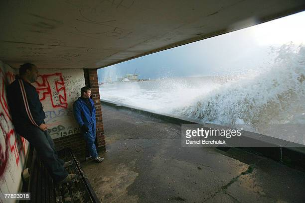 Locals watch as waves crash into the sea wall at Lowestoft on November 9 2007 near Great Yarmouth United Kingdom The fear of widespread flooding in...