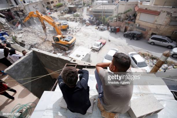 Locals watch Israeli excavators demolish a Palestinian building for allegedly being unauthorized in Al-Issawiya district of East Jerusalem on May 1,...