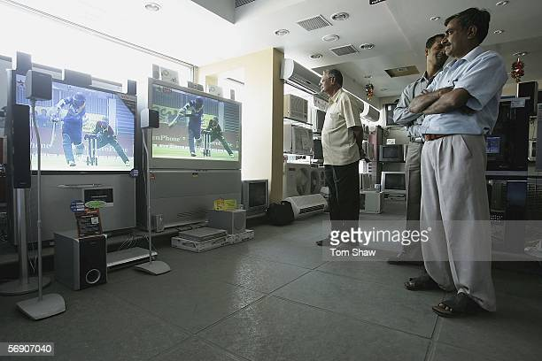 Locals watch the cricket on television at an Electical showroom on February 22 2006 in Baroda India