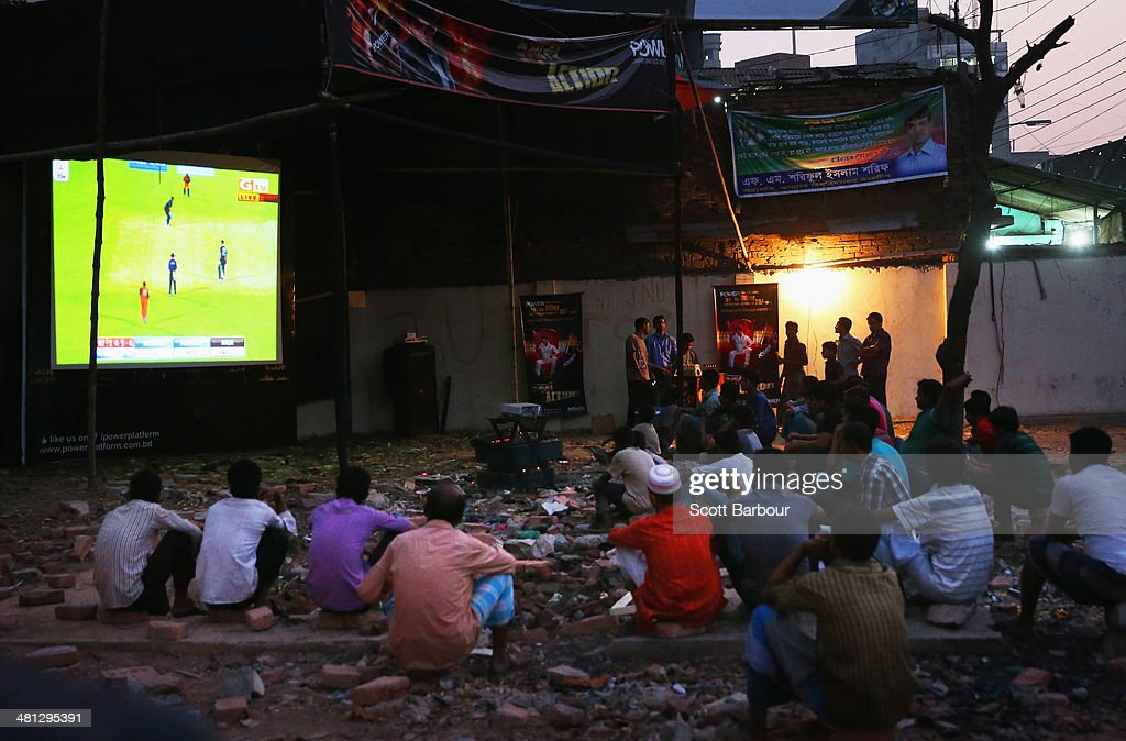Locals watch the ICC World Twenty20 Bangladesh 2014 Group 1 match between New Zealand and the Netherlands on a large television screen showing the match in Old Dhaka on March 29, 2014 in Dhaka, Bangladesh.