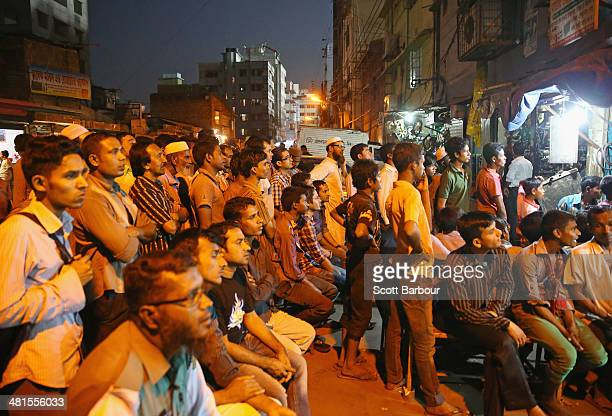 Locals watch the ICC World Twenty20 Bangladesh 2014 match between India v Australia on a television screen in a local shop outside of Sher-e-Bangla...