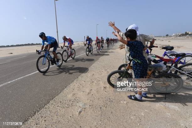 Locals wave as cyclists compete during the second stage of the UAE cycling tour in Abu Dhabi on February 25, 2019.