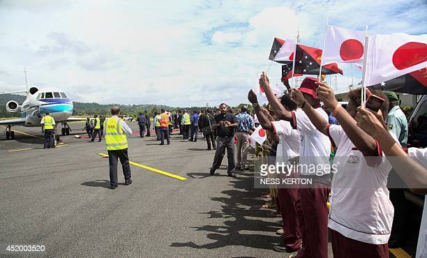 Locals wave Japanese flags as they wait for Japan's Prime Minister Shinzo Abe to disembark from his plane during a visit to Wewak in Papua New Guinea...