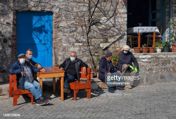locals wearing masks sitting in a coffee shop in barbaros village. - emreturanphoto stock pictures, royalty-free photos & images