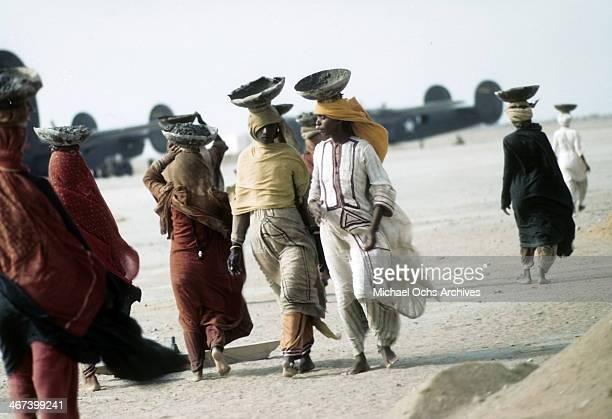 Locals women walk past the U.S. Army Air Force Base in Karachi,India.