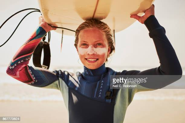 A location portrait of a young surfer girl with her surfboard on the beach.