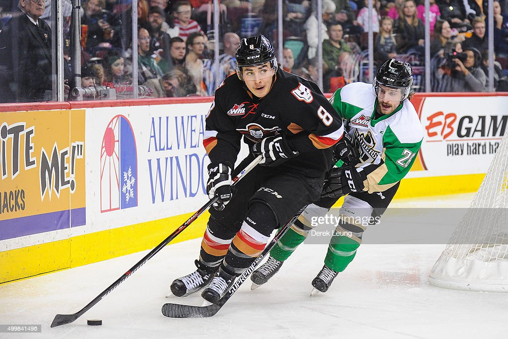 Loch Morrison #8 of the Calgary Hitmen skates with the puck past Kolten Olynek #26 of the Prince Albert Raiders during a WHL game at Scotiabank Saddledome on December 3, 2015 in Calgary, Alberta, Canada.