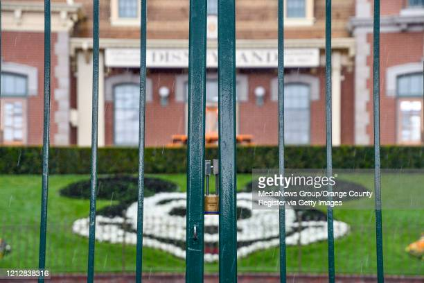 A lock hangs on the center gate between the turnstiles at the entrance to Disneyland in Anaheim CA on Monday Mar 16 2020 The entire Disneyland Resort...