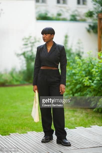 Loïcka Grâce wears a cropped black blazer jacket, black matching suit pants, black leather shoes, a golden nekclace, a bag, during the Twilly By...