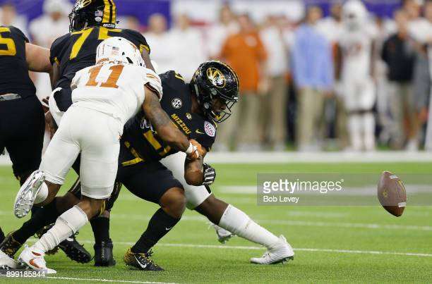 J Locke III of the Texas Longhorns causes Ish Witter of the Missouri Tigers to fumble at NRG Stadium on December 27 2017 in Houston Texas