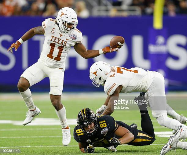 J Locke III of the Texas Longhorns comes up with the ball as Antwuan Davis lays a hit on Albert Okwuegbunam of the Missouri Tigers during the Academy...