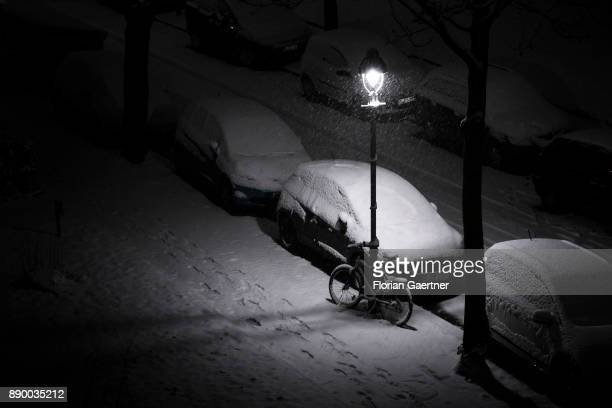 A locked bicycle is pictured during snowfall on December 10 2017 in Berlin Germany