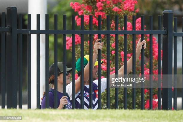 Locked out fans show their support through the fence during the round six AFLW match between the Western Bulldogs and the Fremantle Dockers at...