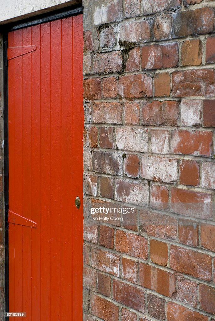 Locked red door and red brick wall : Stock Photo