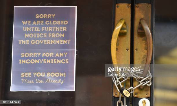 Locked shop displays a sign saying 'sorry we are closed until further notice from the Government, sorry for any inconvenience, see you soon' on April...