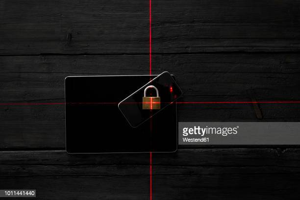 Locked smartphone on digital tablet, symbol for data surveillance